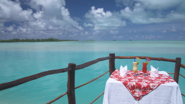 ms, cocktails on resort overwater balcony, aitutaki lagoon, aitutaki, cook islands - aitutaki lagoon stock videos & royalty-free footage
