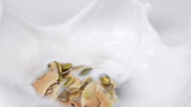 coconut and seeds cluster falling in milk - imperfection stock videos & royalty-free footage