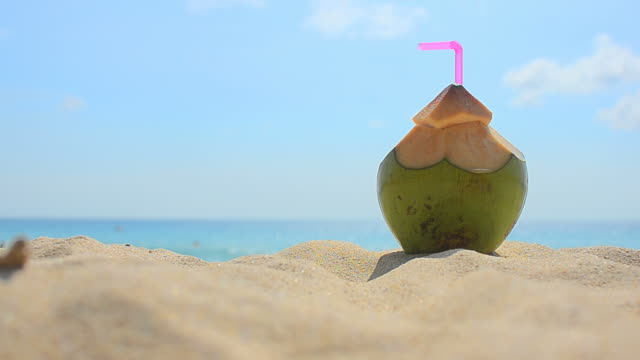 Coconut with drinking straw on a beach