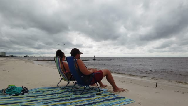 vidéos et rushes de codi thompson and dexter thompson watch the waves while sitting on the beach as tropical storm marco makes its way through the gulf of mexico on... - gulf coast states