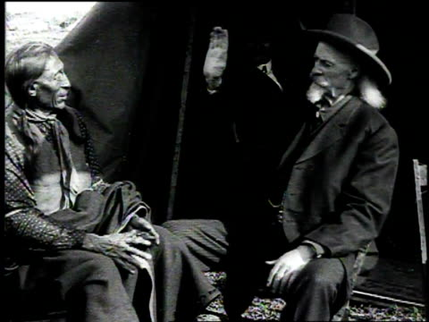 cody and oglala lakota chief iron tail sitting and conversing in sign language / iron tail was one of three models for the fivecent coin buffalo... - ネイティブアメリカン点の映像素材/bロール