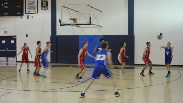 Co-ed high school basketball players competing in a game