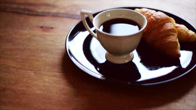 coffee and croissant on wood table