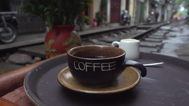 coffee at hanoi train street. iconic image of narrow street with the railway in the middle of the buildings - newly industrialized country stock videos and b-roll footage