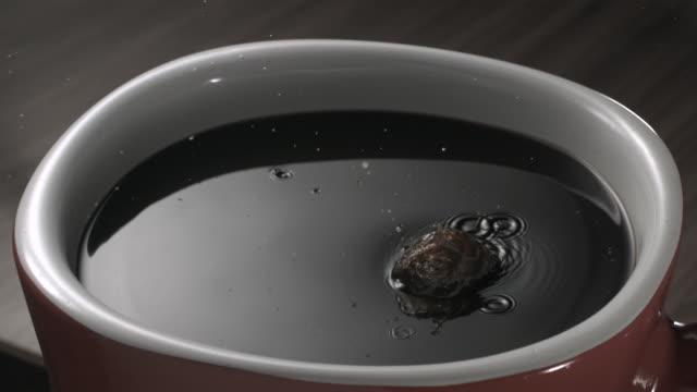 CU SLO MO Coffee bean falling into mug