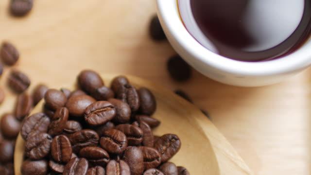 Grãos de café e café preto quente de madeira prato sobre fundo branco de mesa, boneca, atirou-se à esquerda para a direita