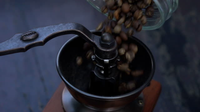 coffee beans are being filled in coffee grinder in slow motion - lactose fermentation stock videos & royalty-free footage