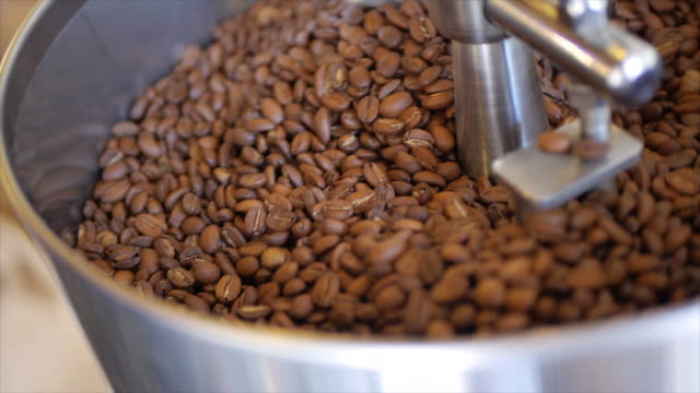 coffee beans are blended and mixed in a roasting machine hopper. - slow motion - roasted coffee bean stock videos & royalty-free footage