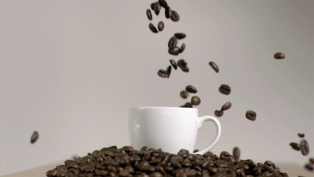 Coffee beans dropping in cup in super slow motion