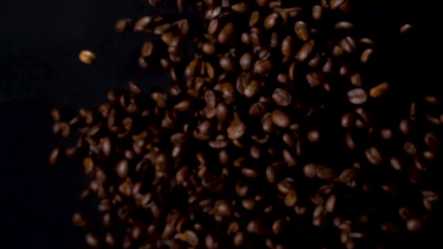 coffee beans explosion to camera in slow motion - fagiolo video stock e b–roll