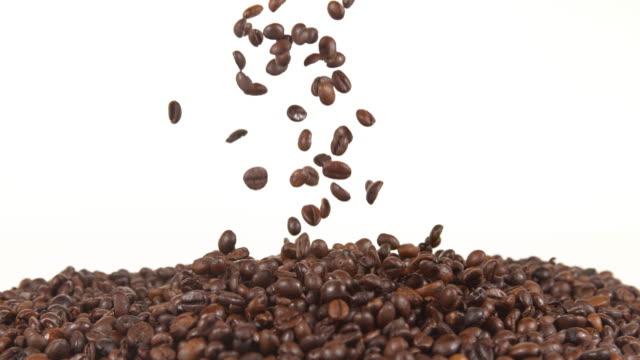 vídeos y material grabado en eventos de stock de coffee beans falling against white background, slow motion 4k - grano de café tostado