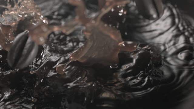cu slo mo coffee beans falling into mug - カップ点の映像素材/bロール
