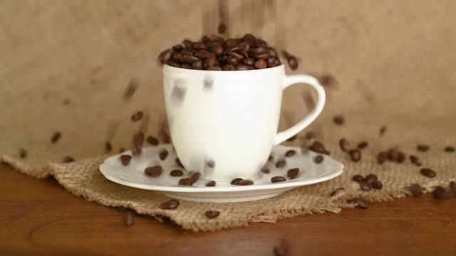 coffee beans falling into the cup - 荒い麻布点の映像素材/bロール