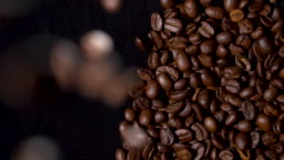 Coffee beans falling on coffee heap