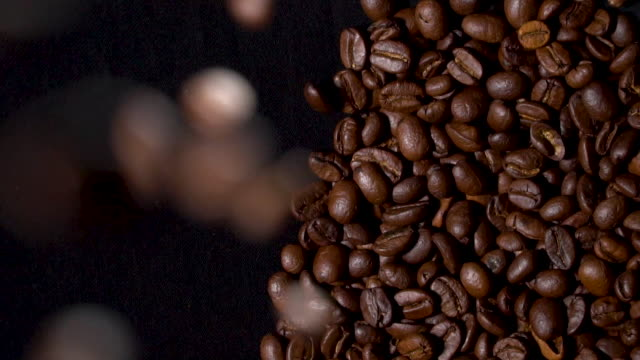 coffee beans falling on coffee heap - roasted coffee bean stock videos & royalty-free footage