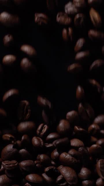 (vertikal) kaffeebohnen füllen sich voll auf schwarzem hintergrund - hoch allgemeine beschaffenheit stock-videos und b-roll-filmmaterial