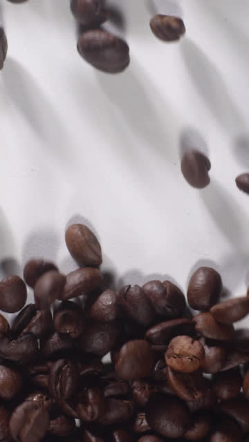 (vertical) coffee beans filling full on white background - vertical stock videos & royalty-free footage