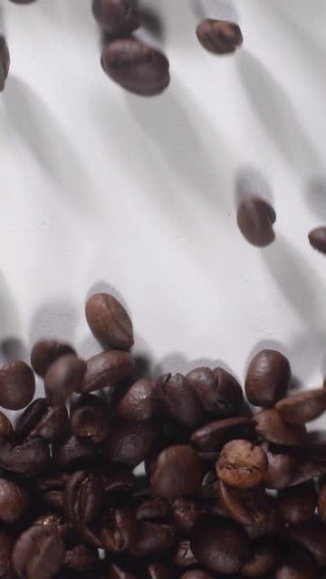 (vertikal) kaffeebohnen füllen sich voll auf weißem hintergrund - hoch allgemeine beschaffenheit stock-videos und b-roll-filmmaterial