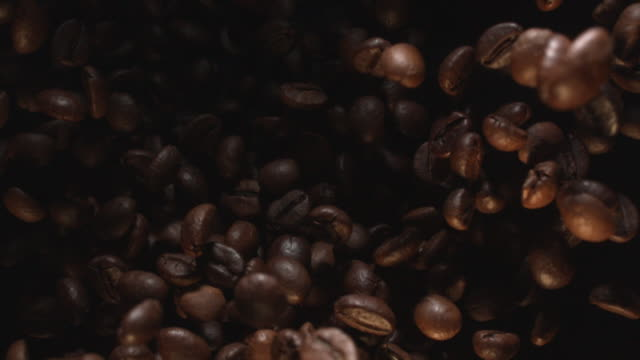 vídeos y material grabado en eventos de stock de coffee beans flying in air in slow motion at 1500 fps on black background - grano planta