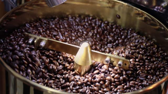Kaffe bönor i kvarnen. Färskt kaffe i kaffe professionell maskin. Arom, bakgrund.