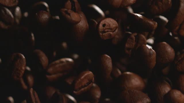 stockvideo's en b-roll-footage met koffiebonen over zwarte achtergrond (super slow motion) - ontslaan