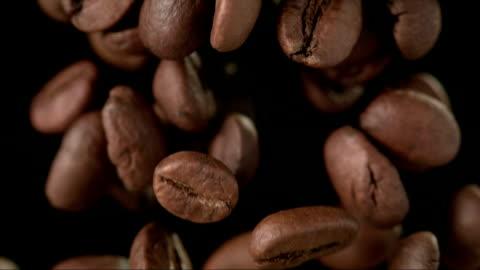 kaffeebohnen auf schwarzem hintergrund (super zeitlupe) - kaffee stock-videos und b-roll-filmmaterial