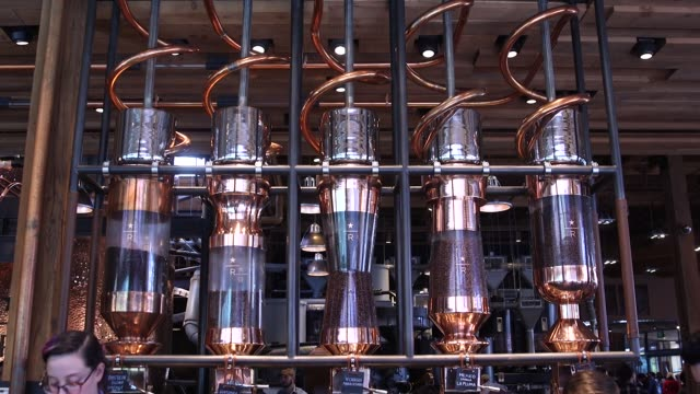 vídeos de stock, filmes e b-roll de coffee beans sit on display inside cylindrical coffee bean dispensing silos at the starbucks reserve roastery and tasting room in seattle wa on... - starbucks