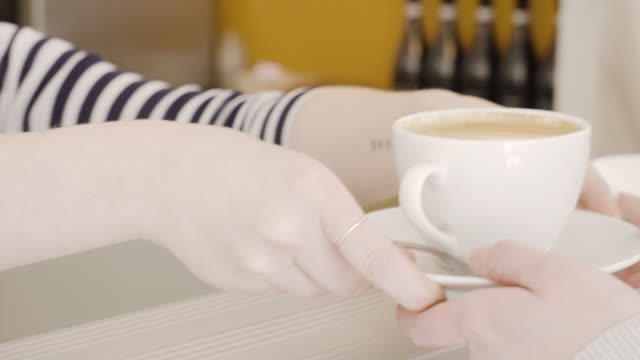 CU of coffee being passed by barista to client.