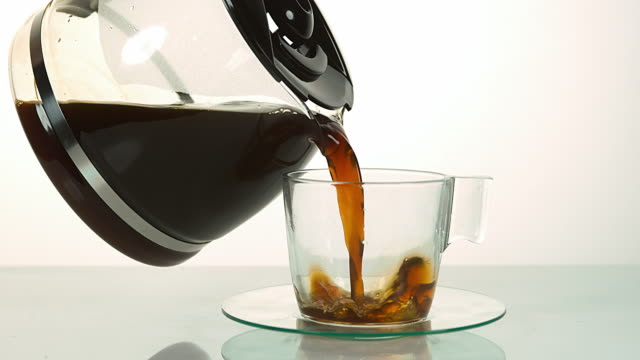 Coffee Being Poured in a Cup against White Background, Slow motion