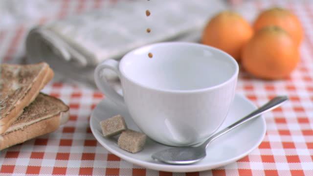 stockvideo's en b-roll-footage met coffee being poured in super slow motion - tafelkleed