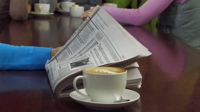 MS Coffee being served to woman reading newspaper / Cape Town, Western Cape, South Africa