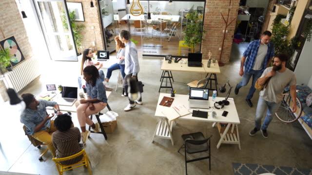 stockvideo's en b-roll-footage met de onderbreking van de koffie bij comfortabel bureau, sommige medewerkers die bij het werk aankomen - freelancer