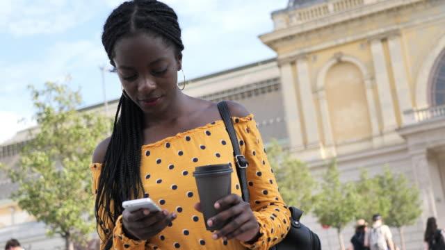 vídeos de stock e filmes b-roll de coffee break for millennial african woman with braided hair - handheld camera - braided hair