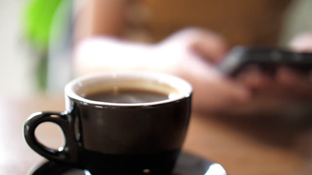 coffee cup at cafe with woman using mobile phone - nightwear stock videos & royalty-free footage