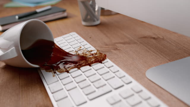 slo mo ld coffee cup hitting a white keyboard and spilling all over it - mistake stock videos & royalty-free footage