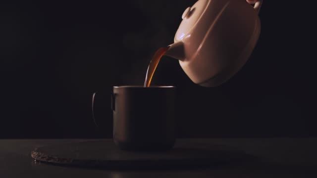 vídeos de stock, filmes e b-roll de copo de café em uma cena mística escura com vapor natural - xícara de café