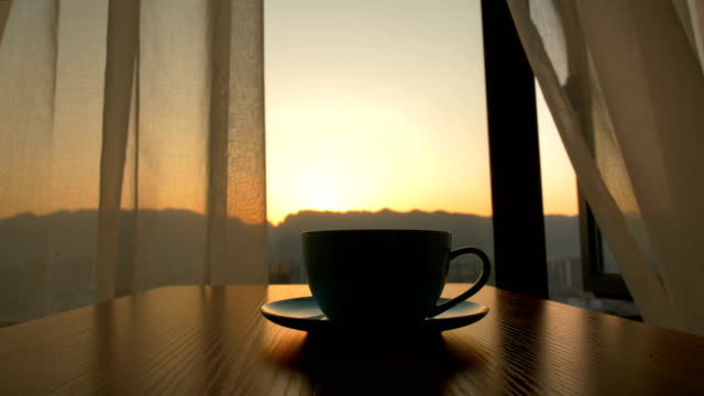 coffee cup on table against background of sunrise - mug stock videos and b-roll footage