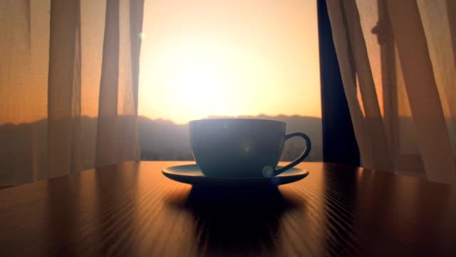 vídeos de stock e filmes b-roll de coffee cup on table in the morning - chávena