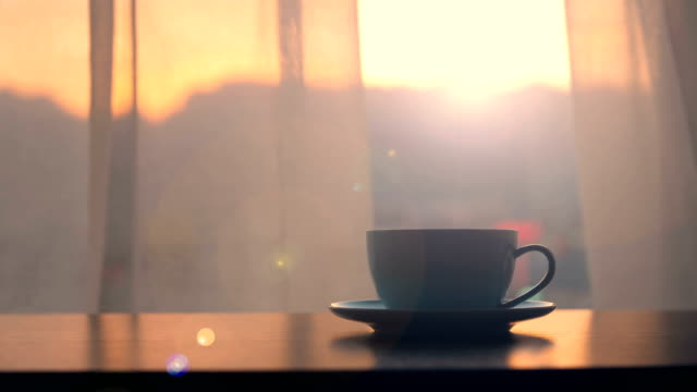 kaffeetasse auf tisch mit sonnenuntergang fensterhintergrund - sonnig stock-videos und b-roll-filmmaterial