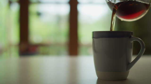 cu coffee cup on the kitchen counter of a home; hot coffee is poured from a glass pot; steam rises from the cup. - elkhorn nebraska stock videos & royalty-free footage