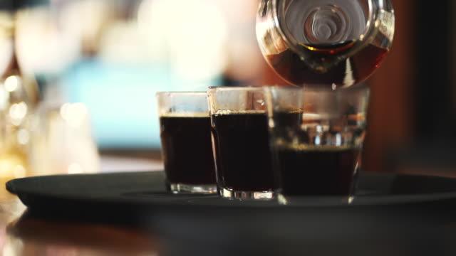 コーヒーカップ、コーヒーをグラスに注ぎ、冷たいビールコーヒー - グラス点の映像素材/bロール