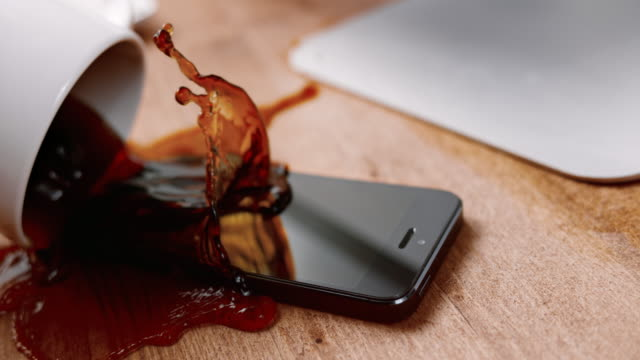 SLO MO LD Coffee cup spilling all over a black mobile phone on the table