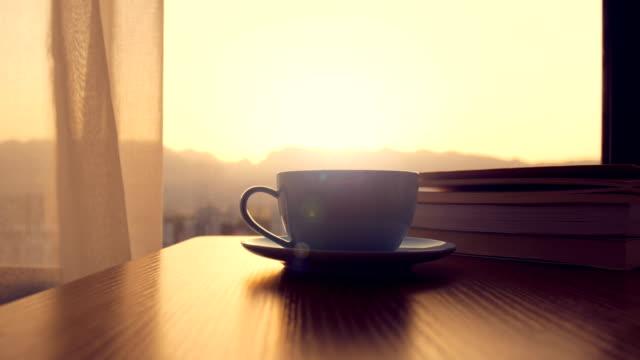 kaffeetasse mit buch auf dem tisch - tee warmes getränk stock-videos und b-roll-filmmaterial