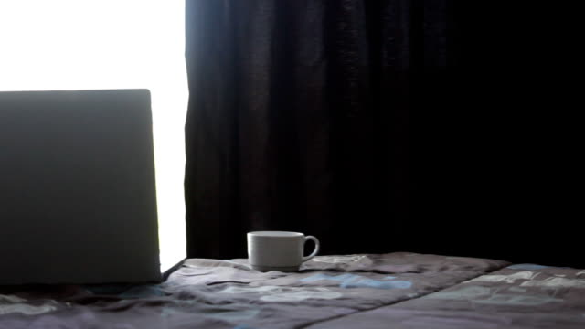 Coffee cup with laptop on the bed