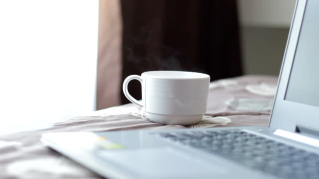 coffee cup with laptop on the bed - coffee cup stock videos & royalty-free footage