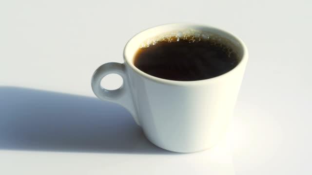 白いテーブルの上の自然な蒸気そして泡が付いているコーヒーカップ
