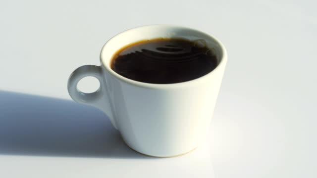 ドリー: ホワイトテーブルに自然な蒸気と泡とコーヒーカップ