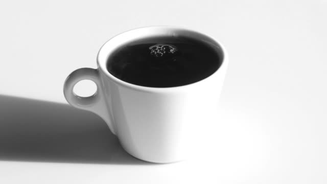 coffee cup with natural steam and bubbles on white table - coffee break stock videos & royalty-free footage