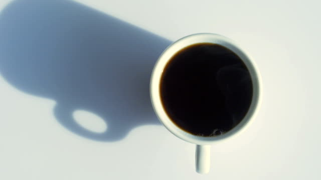 coffee cup with natural steam on white table from directly above - coffee break stock videos & royalty-free footage
