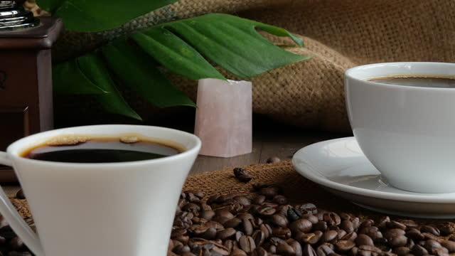 コーヒーカップ、焙煎コーヒー豆、グラインダー、ローズクォーツ石とモンステラは、バーラップの背景と木製のテーブルに残します - 麻袋点の映像素材/bロール